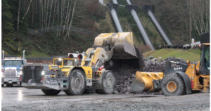 This photo shows rock being removed from the tunnels at the John Hart Dam generating station replacement project site and loaded into a tandem dump truck.